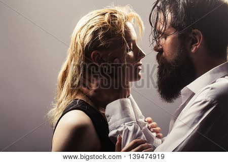 young sexy couple of pretty woman with blonde wet hair and handsome bearded man with long beard embracing on grey studio background