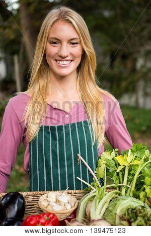 Portrait of happy young female gardener with fresh vegetables in basket at garden