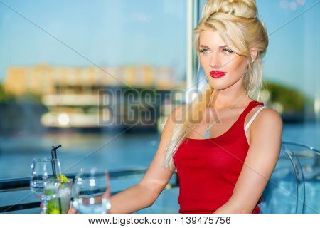 Beautiful blonde woman sits  in restaurant on ship at river in summer city