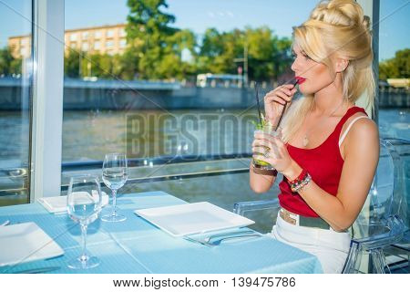 Beautiful blonde woman drinks cocktail in restaurant on ship at river in summer city