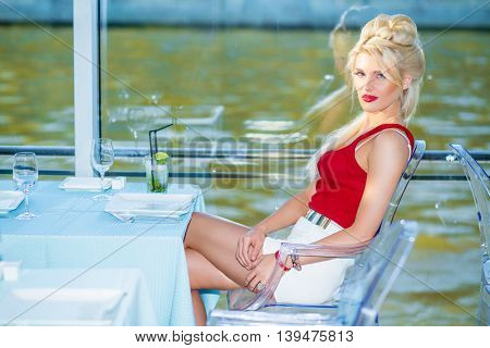 Beautiful blonde woman sits at table with cocktails in restaurant on ship at river
