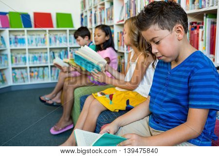 Students reading books while sitting on seats at library in school
