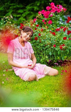 Middle age woman in pink sari and Indian adornment sits on grass in summer park
