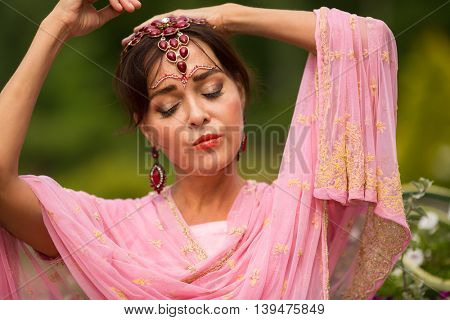 Middle age woman in pink sari and Indian adornment poses in summer park