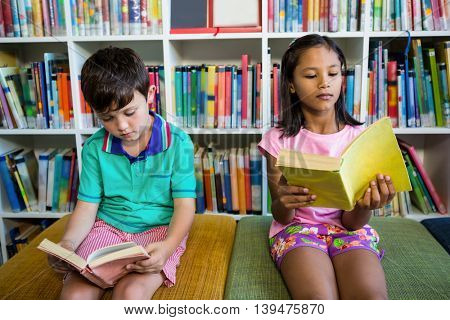 Elementary students reading books in school library
