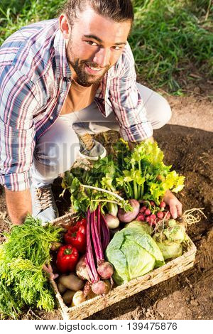 Portrait of happy young hipster gardener crouching with vegetables at garden