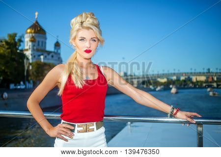 Blonde cute woman in red top on deck of ship at Moscow River near Cathedral