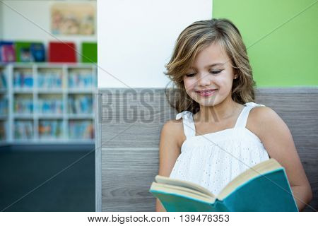 Smiling girl reading book while sitting on bench in school library