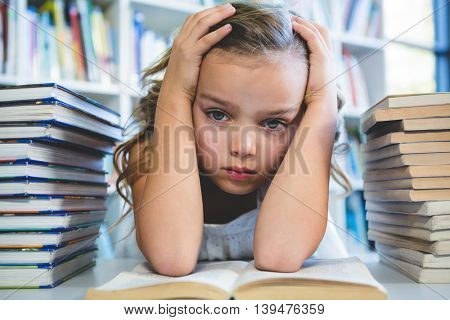 Close-up of stressed girl with head in hand at school library
