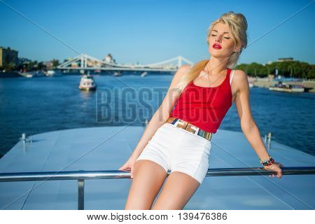 Beautiful blonde woman poses near railing at deck of ship at river in summer city
