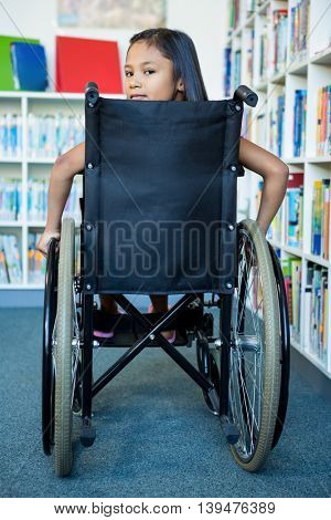 Rear view portrait of handicapped girl on wheelchair at school library