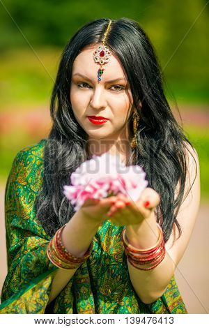 Brunette woman in sari and Indian adornment holds pink flower in summer park