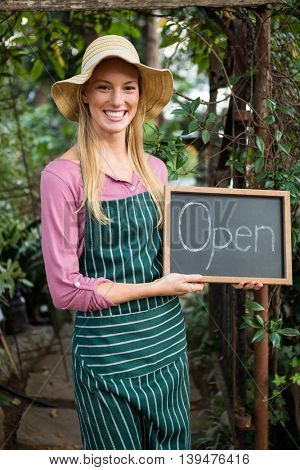 Portrait of happy young female gardener with open text on chalkboard at garden