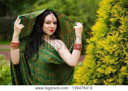 Brunette woman in sari and Indian adornment poses to green bush in park
