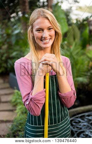 Portrait of beautiful young female gardener with hand tool at garden