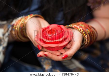 Womans hands with bracelets hold unlit candles in form of roses, Close up