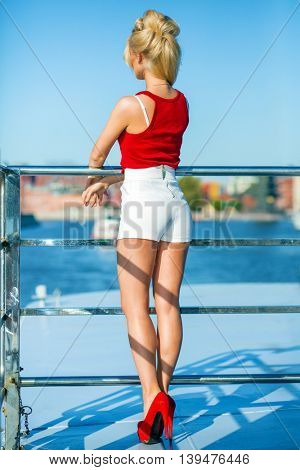 Blonde pretty woman poses on deck of ship at river at summer, back view