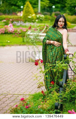 Brunette woman in sari and Indian adornment poses in summer green park