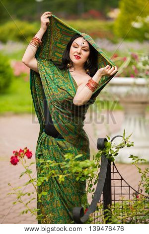 Brunette young woman in sari and Indian adornment poses in garden