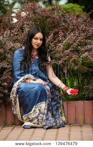 Brunette in blue sari sits near barberry bushes with red burning candle in form of roses