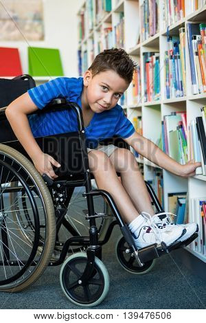Portrait of handicapped boy searching books at library in school