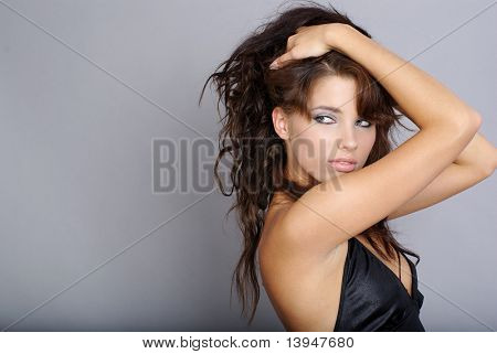 Sexy girl wearing black dress on grey background