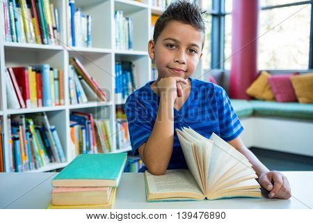 Portrait of boy reading book at table in school library
