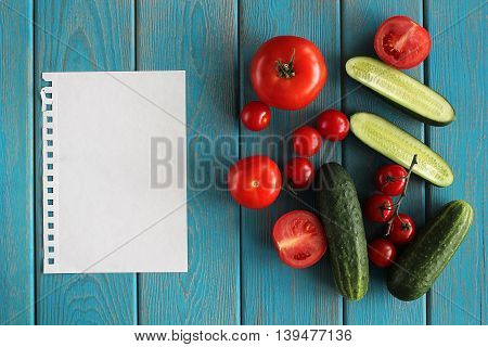 Sheet and composition of vegetables on blue wooden desk. Tomatoes, cucumber. Top view.