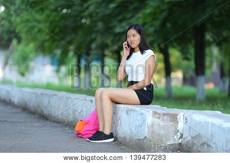 Girl female teenager with black hair in a bob white east Asian woman green park with a backpack background. Lady holds dials push your finger smiling looking into the camera talking on the phone happy.