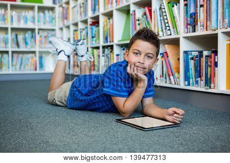 Portrait of boy lying with digital tablet in school library