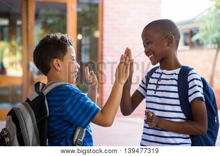Happy classmates giving high-five at school corridor