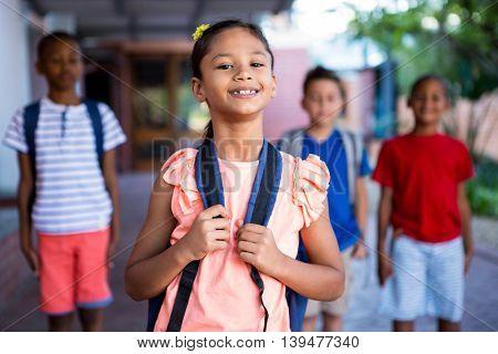 Happy schoolgirl with classmates in background at school corridor