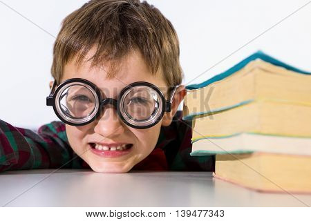 Portrait of playful boy leaning by books on table in classroom