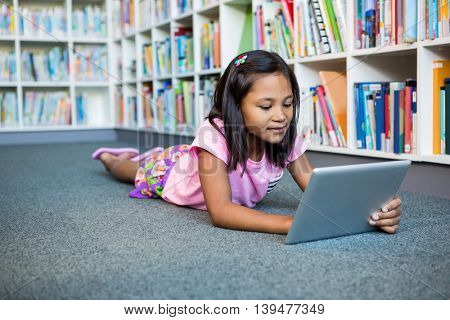 Girl using digital tablet while lying in school library