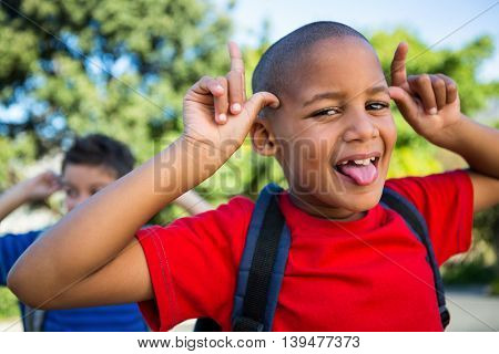 Portrait of playful schoolboy making a face at school campus