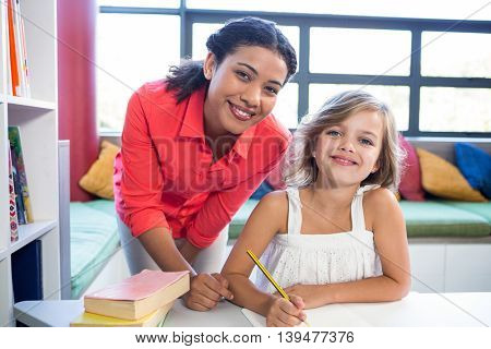 Portrait of young teacher with girl in school library
