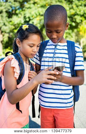 Front view of schoolboy and girl using mobile phone at campus