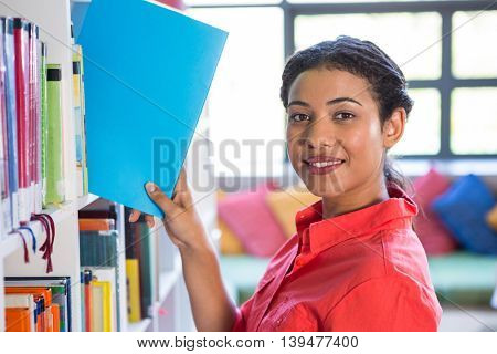 Portrait of smiling teacher removing book from bookshelf at library in school