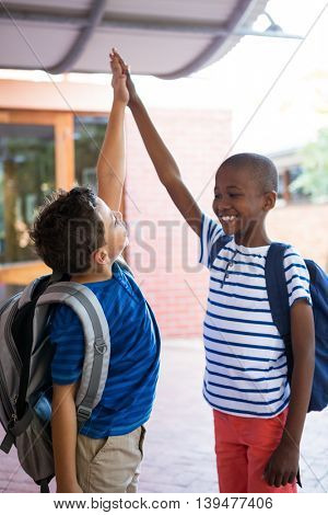 Playful classmates giving high-five at school corridor