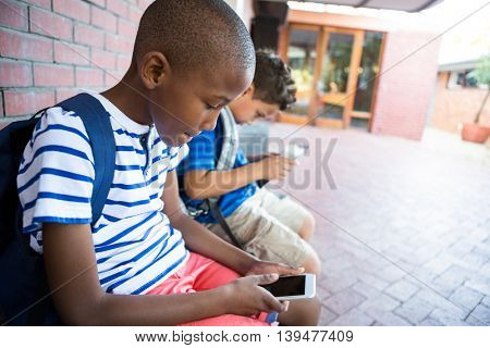 Schoolboys using mobile phones while sitting at corridor in school