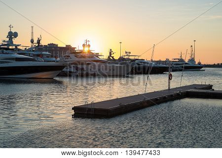 Yachts standing  in a port at  sunset