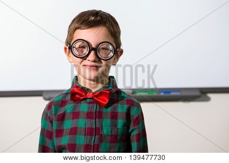 Portrait of smiling boy standing against whiteboard in classroom