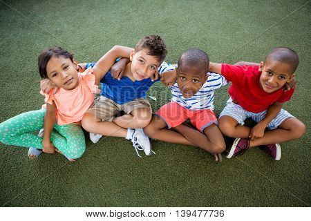 High angle portrait of happy children sitting on grass at park