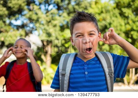 Portrait of schoolboy making a face at school campus