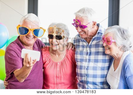 Seniors taking a selfie with funny glasses in a retirement home