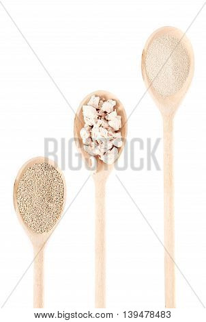Three wooden spooins with fresh pressed yeast, dry yeast and nstant dry yeast isolated on white background. Yeast is a main ingredient of fresh bread dough, pizza dough and many other dough's.