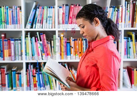 Side view of teacher reading book at library in school