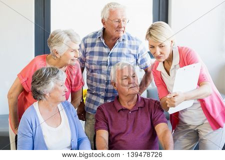 Nurse showing clipboard to seniors in a retirement home