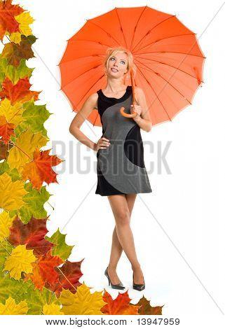 Woman with orange umbrella. Leaves background