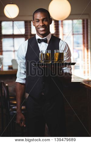Portrait of bartender holding serving tray with glasses of beer